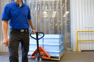 Worker pulling inventory on hand truck on loading dock